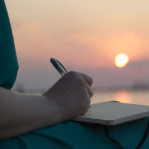 woman writing sunset